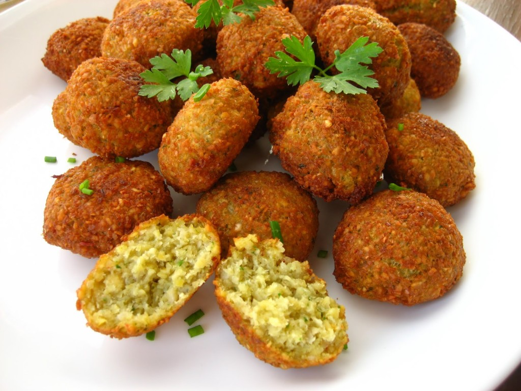 "falafel is a deep-fried ball or patty made from ground chickpeas, fava beans, or both. Falafel is a traditional Middle Eastern food, commonly served in a pita, which acts as a pocket, or wrapped in a flatbread known as lafa; ""falafel"" also frequently refers to a wrapped sandwich that is prepared in this way. The falafel balls are topped with salads, pickled vegetables, hot sauce, and drizzled with tahini-based sauces. Falafel balls may also be eaten alone as a snack or served as part of a meze (appetizers)."