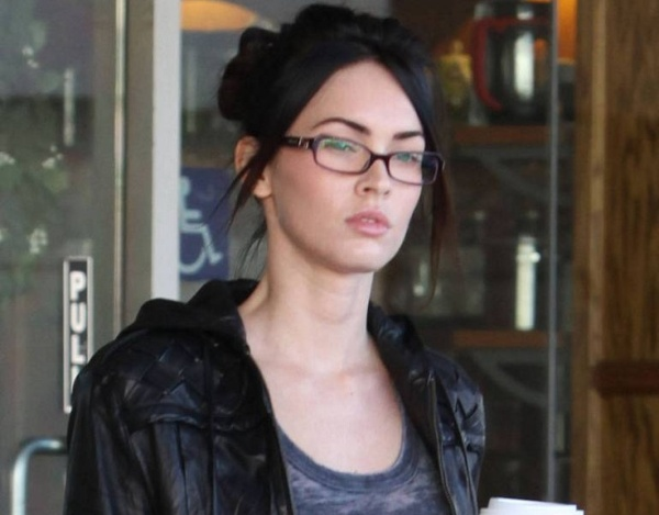 stunning megan fox with spectacles and coffee running out from a cafe