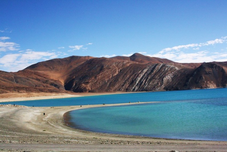 """Pangong Tso Tibetan for """"long, narrow, enchanted lake"""", also referred to as Pangong Lake, is an endorheic lake in the Himalayas situated at a height of about 4,350 m (14,270 ft). It is 134 km (83 mi) long and extends from India to Tibet. Approximately 60% of the length of the lake lies in Tibet. The lake is 5 km (3.1 mi) wide at its broadest point. All together it covers 604 km2. During winter the lake freezes completely, despite being saline water. It is not part of Indus river basin area and geographically a separate land locked river basin"""